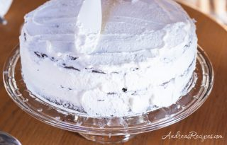 Spreading a crumb coat of whipped cream on a Black Forest cake - Andrea Meyers