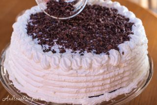 Sprinkling chocolate shavings on top of a Black Fores cake - Andrea Meyers